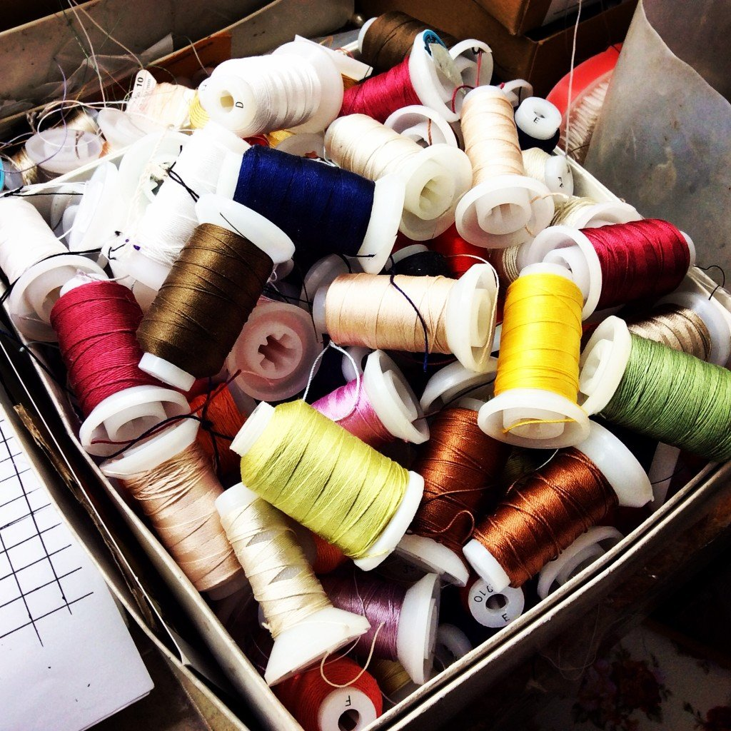 Spools of different color silk thread for beading and stringing.